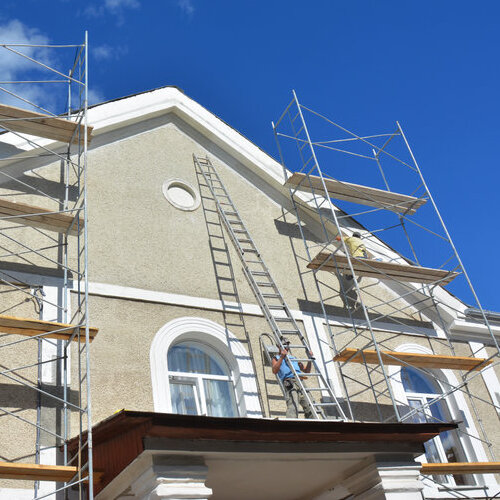 A home's exterior being painted beige.