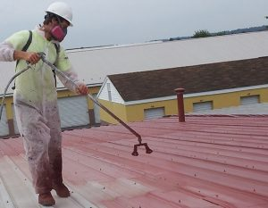 A Roofing Restoration Professional Sprays a Roof