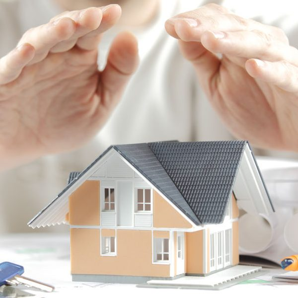 Home Insurance Concept - Close up Hands Covering Miniature Model House on the Table with Keys and Blueprints on the Sides