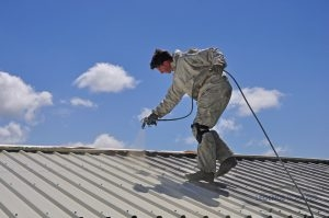 A Roofing Expert Sprays a Restorative Roof Coating