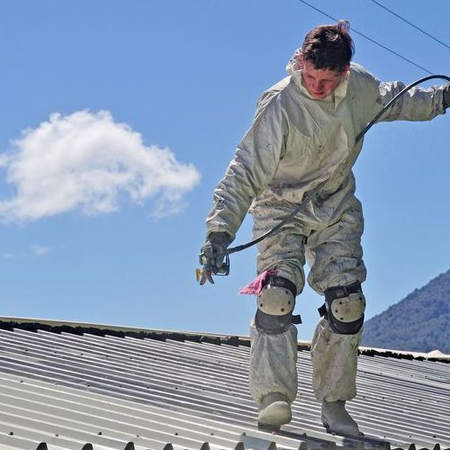 spraying roof coating on building